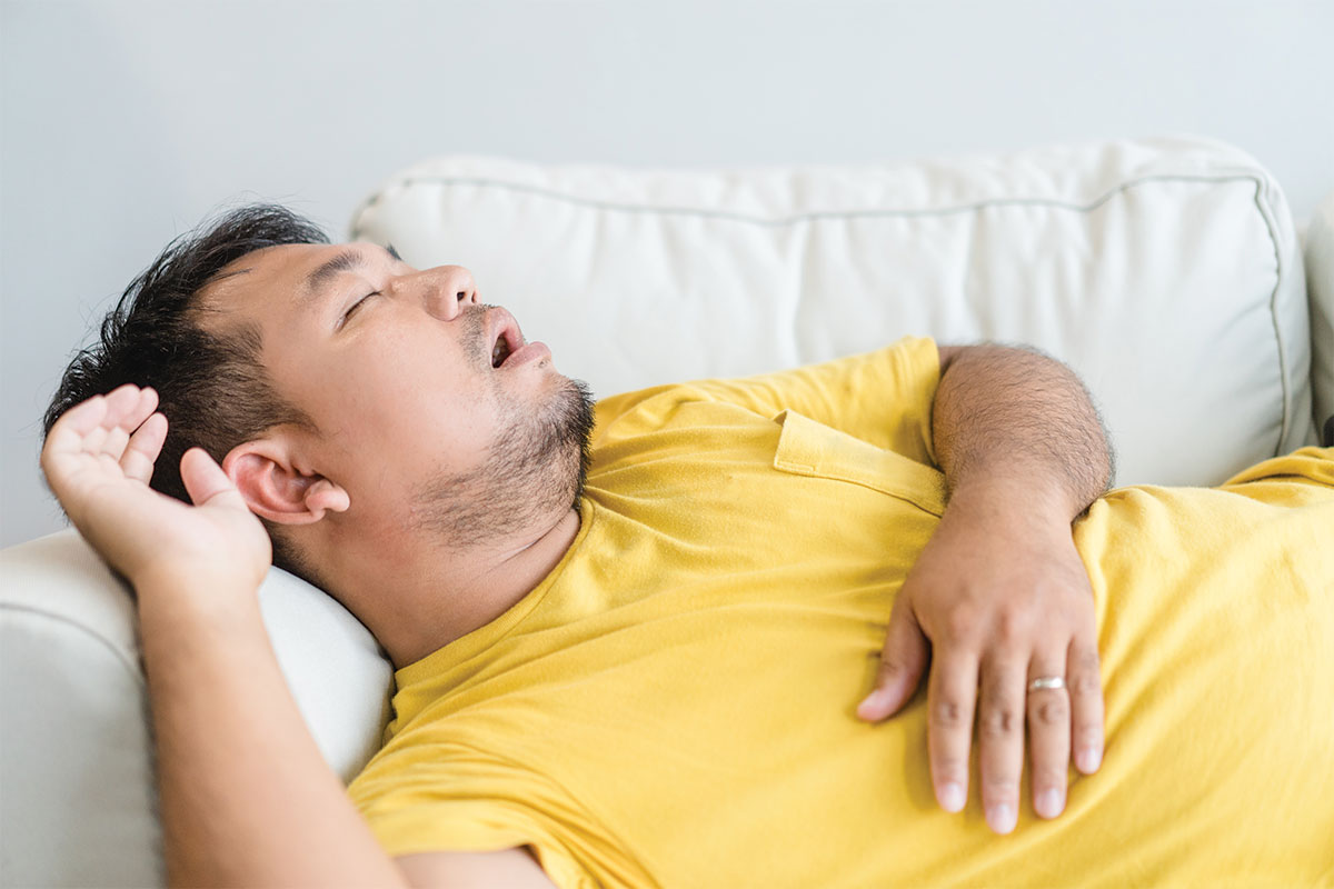 Why do people snore? Man snoring on couch while aslseep.